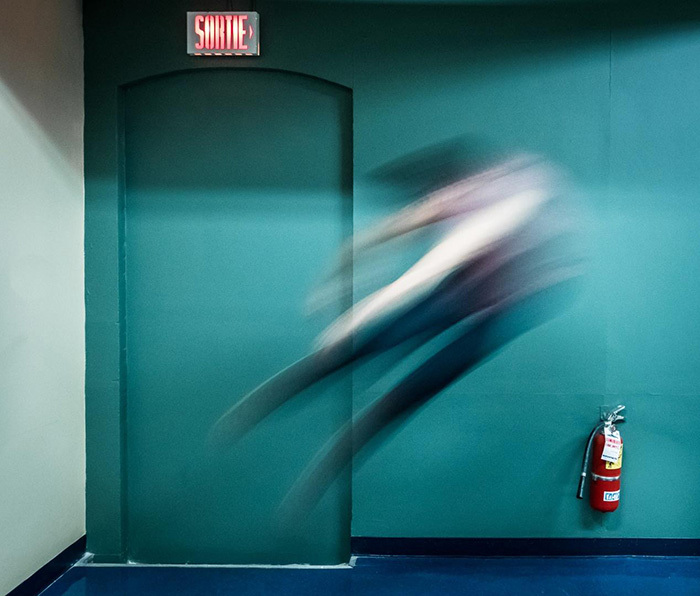 A blured person jumping backwards in a hallway near an emergency exit and a fire extinguisher