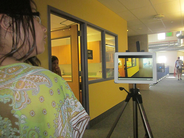 A student in the school's halls filming with an iPad